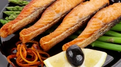 Grilled salmon slices with asparagus lemon and olives Stock Footage