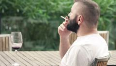 Young, pensive man smoking cigarette sitting on terrace Stock Footage