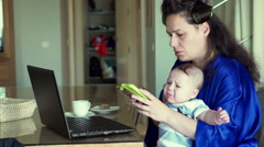 Mother with laptop talking on cellphone and child disturbing her Stock Footage