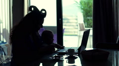 Young mother with baby drinking coffee by table at home Stock Footage