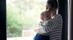 Young mother holding and kissing her child by window at home Stock Footage