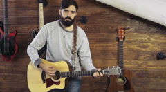 Handsome bearded man playing the acoustic guitar slow motion Stock Footage