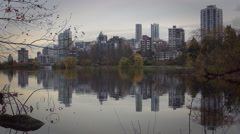 Vancouver's skyline is reflected in lost lagoon as ducks float by Stock Footage
