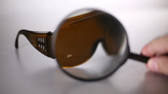 Close-up of brown laser safety glasses. Spots after laser treatment. Stock Footage