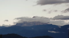 Time-lapse of clouds churning over a mountain peak at sunset. - stock footage