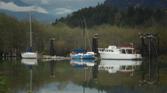 Moored boats floating and their reflections in crystal calm waters. Stock Footage