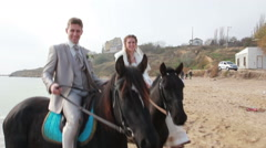 Newlyweds walking along the beach on horseback at the wedding Stock Footage