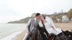 Bride and groom walking along the beach on horseback at the wedding Stock Footage