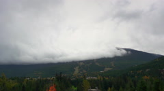 Time-lapse of dark storm clouds churning over Blackcomb Mountain in autumn Stock Footage