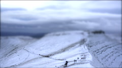 Walkers on Snow Covered Mountain Summit. Tilt Shift Timelapse Stock Footage