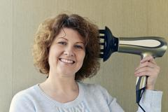 Woman doing curls with  hairdryer and diffuser - stock photo