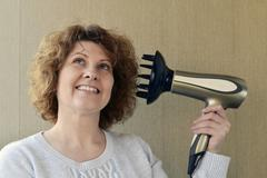 Woman doing curls with  hairdryer and diffuser Stock Photos