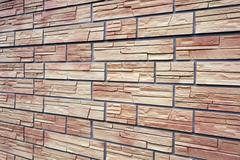 A decorative stone artificial covering in the form of red bricks. Stock Photos