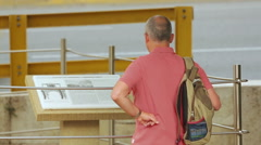 Male tourist reads information at open air museum, sightseeing tour on vacation Stock Footage