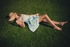 Young woman on grass being rude - stock photo
