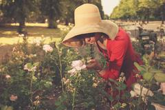 Young woman standing amongst roses in park Stock Photos