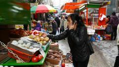Asian woman talk on phone choose potatoes on street market tray Stock Footage