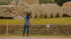 Young female tourist taking picture of huge column remains, sightseeing tour Stock Footage