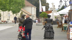 Stock Video Footage of People walking and passing by statues and street stalls in Alba Iulia