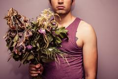 Young man holding bouquet of dead flowers Stock Photos