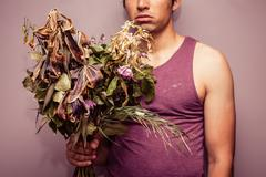 Young man holding bouquet of dead flowers - stock photo