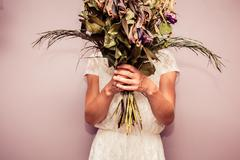 Young woman holding bouquet of dead flowers - stock photo