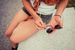 Woman mending broken sunglasses outside - stock photo