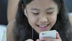 Happy Asian girl listening music with smartphone, Pan shot Stock Footage