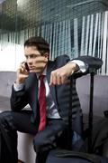 Businessman on phone during business travel - stock photo