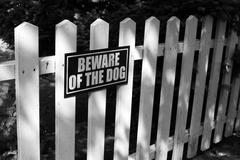 Beware of dog sign on white picket fence Stock Photos