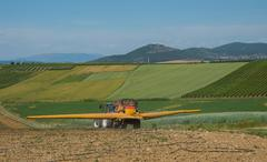 Italy, Umbria, Tractor fertilizing field in valley - stock photo