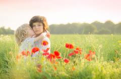 Boy standing in a field kissing his brother Stock Photos