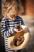 Small blond boy holding pine cone - stock photo