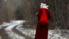 Santa Claus going down the road in the woods Stock Footage