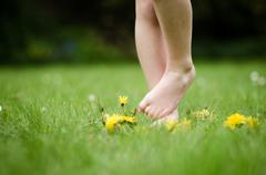 Child's (6-7) bare feet among grass and dandelions - stock photo