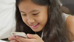 Happy Asian girl listening music with smartphone, Tilt up shot Stock Footage