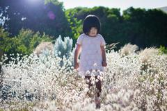 Small girl wearing white dress walking in field with high blossoming grass, - stock photo