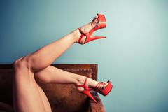 Woman in stripper heels on sofa - stock photo
