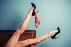 Seductive woman in heels on sofa - stock photo