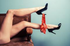 Seductive woman in heels on sofa - stock photo