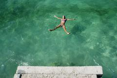 Croatia, Dalmatia, Trogir, Mid-adult woman floating in green sea - stock photo