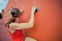 Young woman bouldering - stock photo
