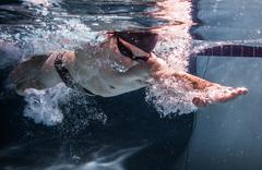 Underwater shot of a man swimming in a pool Stock Photos