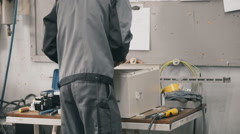 Factory male technician install electrical steel cabinet all the components of Stock Footage