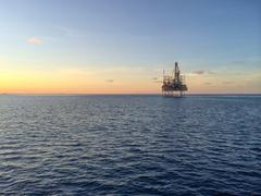 Oil rig at sunset - stock photo