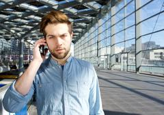 Stock Photo of Serious young man talking on mobile phone inside building
