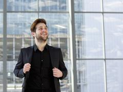 Trendy young man in black business suit - stock photo