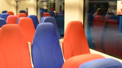 Interior of an empty train with red and blue seats Stock Footage