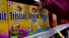 Woman selecting Triscuit low sodium cookie in grocery store Stock Footage