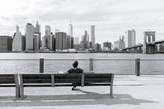 The man sits and admire of the downtown of New York. - stock photo